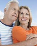 Пары обнимая и усмехаясь Outdoors стоковая фотография
