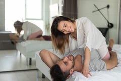 Пары обнимая лежать в кровати, молодой женщине сидят на человеке в спальне стоковые изображения