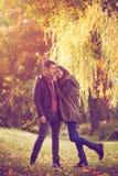 Пары обнимая на красочном лесе осени стоковое изображение
