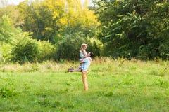Пары обнимая на природе Молодой романтичные человек и женщина стоя и обнимая один другого с нежностью outdoors Молодые Стоковое Изображение RF