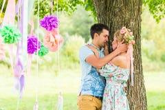 Пары обнимая на сельской местности Молодой романтичные человек и женщина стоя и обнимая один другого с нежностью дальше Стоковое Фото