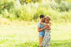 Пары обнимая на сельской местности Молодой романтичные человек и женщина стоя и обнимая один другого с нежностью дальше Стоковые Фотографии RF