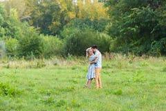 Пары обнимая на сельской местности Молодой романтичные человек и женщина стоя и обнимая один другого с нежностью дальше Стоковое фото RF