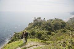 Пары обнимая на скале пока смотрящ вид на океан Стоковое Изображение