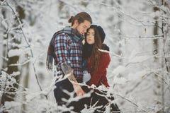 Пары обнимая один другого в лесе зимы Стоковые Изображения