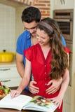 Пары обнимая пока проверяющ книгу рецепта Стоковые Фото
