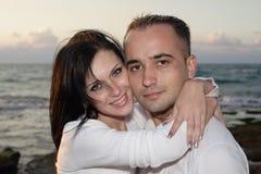 пары обнимая романтичный заход солнца Стоковое Изображение