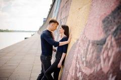 Пары обнимая рядом с стеной граффити стоковая фотография rf