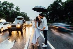 Пары обнятые под зонтиком идут дождь, стойки на дороге Автомобили проходят мимо Стоковая Фотография RF