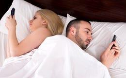 Пары общаясь с мобильными телефонами в кровати Стоковая Фотография