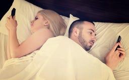 Пары общаясь с мобильными телефонами в кровати Стоковое Фото