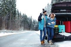 Пары около открытого багажника автомобиля вполне багажа на дороге, космосе для текста стоковая фотография rf