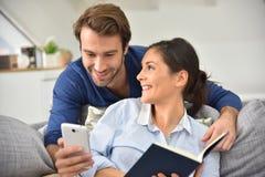 Пары дома используя smartphone и книгу чтения Стоковые Фотографии RF