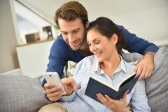 Пары дома используя smartphone и книгу чтения Стоковое Изображение RF