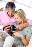 Пары дома смотря фото на камере Стоковое Изображение RF