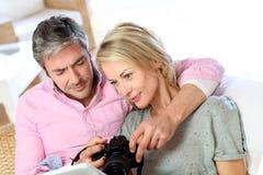 Пары дома смотря фото на камере Стоковое Изображение