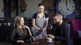 Пары оплачивая с телефоном для обедающего Молодые пары сидя в ресторане и мужчина оплачивая для обедающего с телефоном видеоматериал