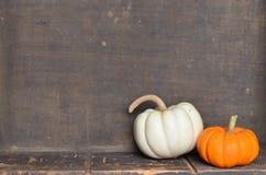 Пары оранжевых и белых тыкв на деревянной предпосылке Стоковое Фото