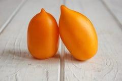 Пары оранжевых томатов на белой деревянной доске Стоковые Изображения RF