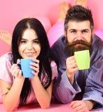 Пары ослабляют в утре с кофе Концепция традиции семьи Человек и женщина на усмехаясь положении сторон, розовой предпосылке Стоковое фото RF