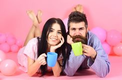 Пары ослабляют в утре с кофе Пары в кофе питья влюбленности в кровати Человек и женщина на усмехаясь положении сторон, розовом Стоковое фото RF