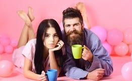 Пары ослабляют в утре с кофе Человек и женщина на усмехаясь положении сторон, розовой предпосылке Концепция утра выходных Стоковое Изображение RF