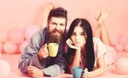 Пары ослабляют в утре с кофе Человек и женщина на усмехаясь положении сторон, розовой предпосылке Концепция утра выходных стоковые изображения rf