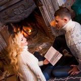 Пары ослабляя дома читающ книгу Ноги в шерстях socks около камина Концепция зимнего отдыха Стоковое Изображение RF