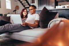 Пары ослабляя на софе дома с компьтер-книжкой Стоковые Изображения
