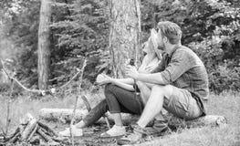 Пары ослабляя сидят на журнале имея закуски Дата пикника похода Семья наслаждается романтичными выходными в природе Приятный пикн стоковые изображения rf
