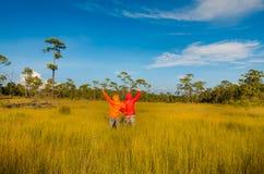 Пары оставаясь с поднятыми руками на пшеничном поле Стоковые Изображения RF