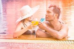 Пары ослабляя в бассейне курорта с коктеилями Стоковые Изображения