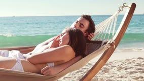 Пары ослабляя в гамаке на пляже видеоматериал
