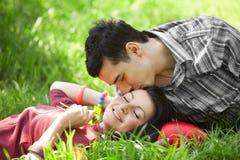 Пары ослабляя на зеленой траве Стоковая Фотография