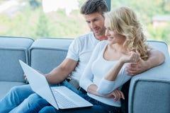 Пары ослабляя на софе используя компьтер-книжку Стоковое Фото