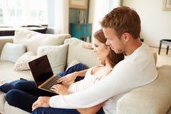 Пары ослабляя на софе используя портативный компьютер совместно Стоковая Фотография