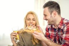 Пары ослабляя дома и есть пиццу Стоковые Изображения RF
