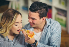 Пары ослабляя дома и есть пиццу Стоковая Фотография RF
