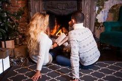 Пары ослабляя дома читающ книгу Ноги в шерстях socks около камина Концепция зимнего отдыха Стоковая Фотография