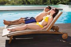 Пары отдыхая на loungers солнца бассейном Стоковая Фотография RF