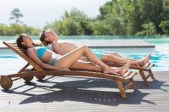 Пары отдыхая на loungers солнца бассейном Стоковое фото RF