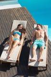 Пары отдыхая на loungers солнца бассейном Стоковые Изображения RF