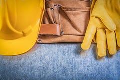 Пары перчаток безопасности оборудуют шлем здания пояса на металлической задней части Стоковое Фото