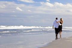 пары пляжа укомплектовывают личным составом романтичную женщину прогулки Стоковое фото RF