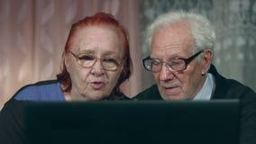 Пары пожилых людей компьтер-книжки просмотра 2 съемки акции видеоматериалы