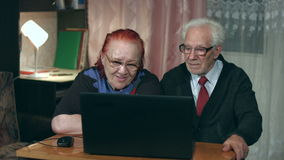 Пары пожилых людей компьтер-книжки просмотра видеоматериал