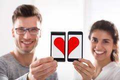 Пары показывая форму сердца на сотовом телефоне стоковые изображения rf