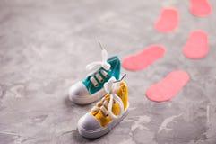 Пары покрашенных зашнурованных gumshoes и красные следы ноги на старом сером цементе Стоковое Фото