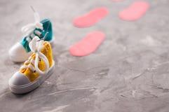 Пары покрашенных зашнурованных gumshoes и красные следы ноги на старом сером цементе с космосом экземпляра Стоковое Фото