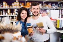 Пары покупая инструменты для улучшений дома в поставках краски Стоковое Изображение